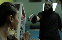 Gallery image from movie. A guy holds a woman at gunpoint.