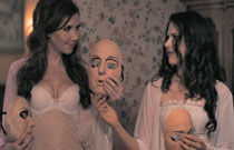 Gallery image from movie. Two girls in their bras holding creepy masks.