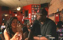 Gallery image from movie. Two people having drinks.