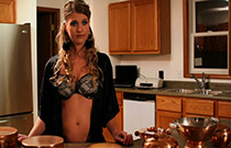 Gallery image from movie. Girl in bra stands in kitchen