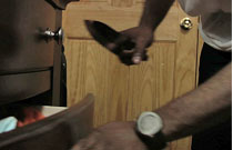 Gallery image from movie. A man gets a knife from his drawer.