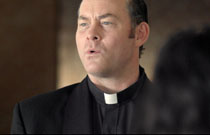 Gallery image from movie. David Koechner as a priest.